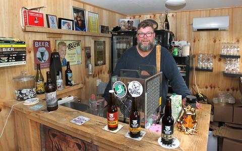 Bernd Beersma achter zijn eigen tap. Op de voorgrond een paar van zijn zelf gebrouwde bieren.